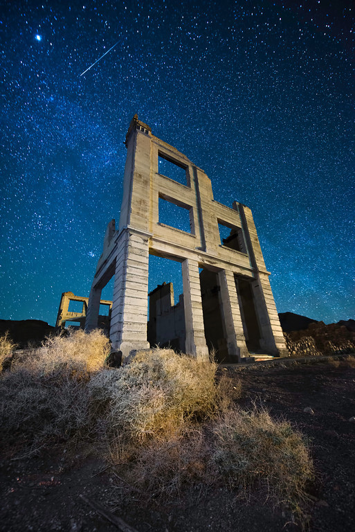 The historic Cook Bank building in the ghost town of Rhyolite, Nevade under the night sky.