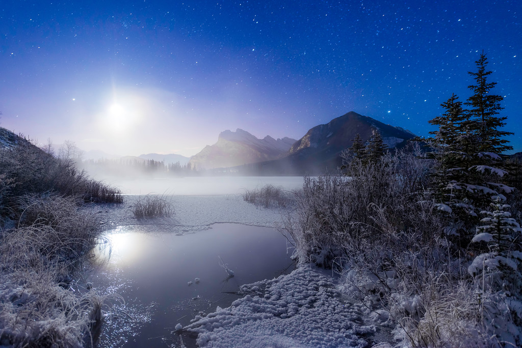 The partially frozen Vermilion Lake beneath the moon light in Banff, Alberta, Canada.