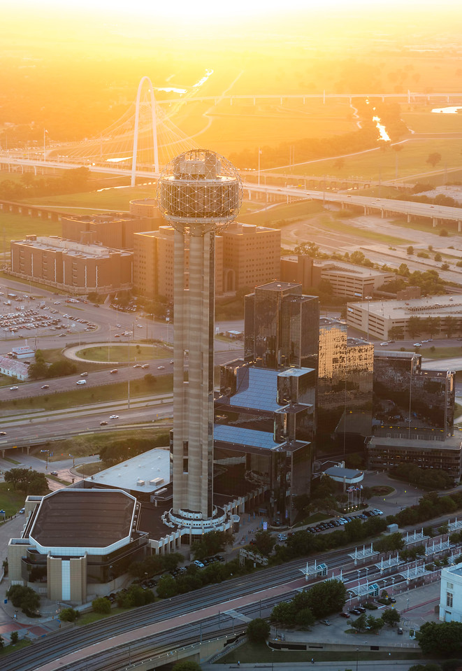 Reunion Tower and the Hyatt Regency in downtown Dallas at sunset. Also pictured in the background is the Margaret Hunt Hill Bridge.